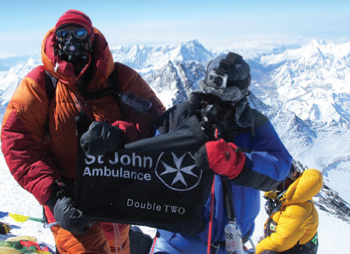 Company flag at the top of mount everest with St John Ambulance